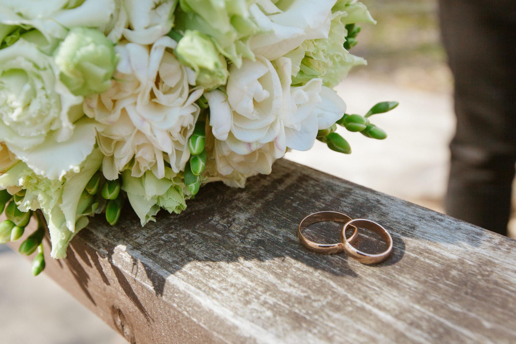 Meine Hochzeit. Mein Tag. Trauringe neben Blumenstrauß